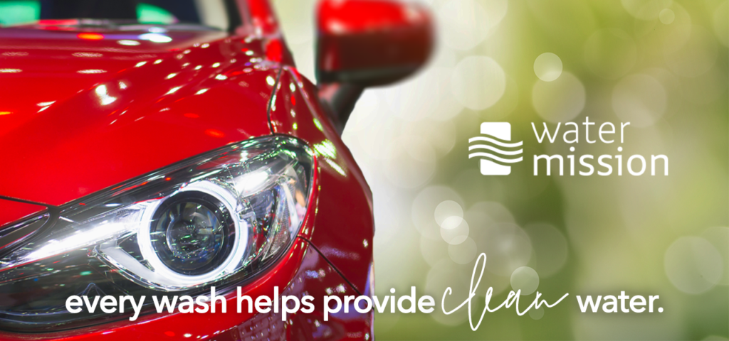 """A shiny red car with Water Mission logo next to it. The text on it reads """"every wash helps provide clean water""""."""